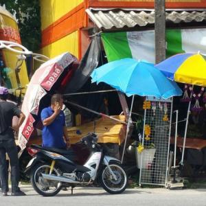 Phuket parked tour bus rolls off, crunches pickup, shopfront